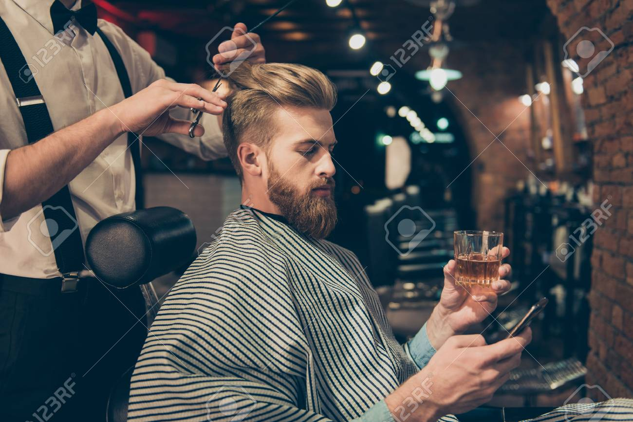Chill out at the barber shop. Side view of handsome young red bearded man drinking scotch and browsing at his pda, while getting a haircut - 82694152