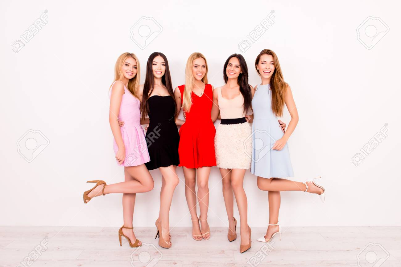 Full Length Of Excited Girlfriends In Colorful Short Cocktail Dresses Are Ready For Birthday Celebration Party