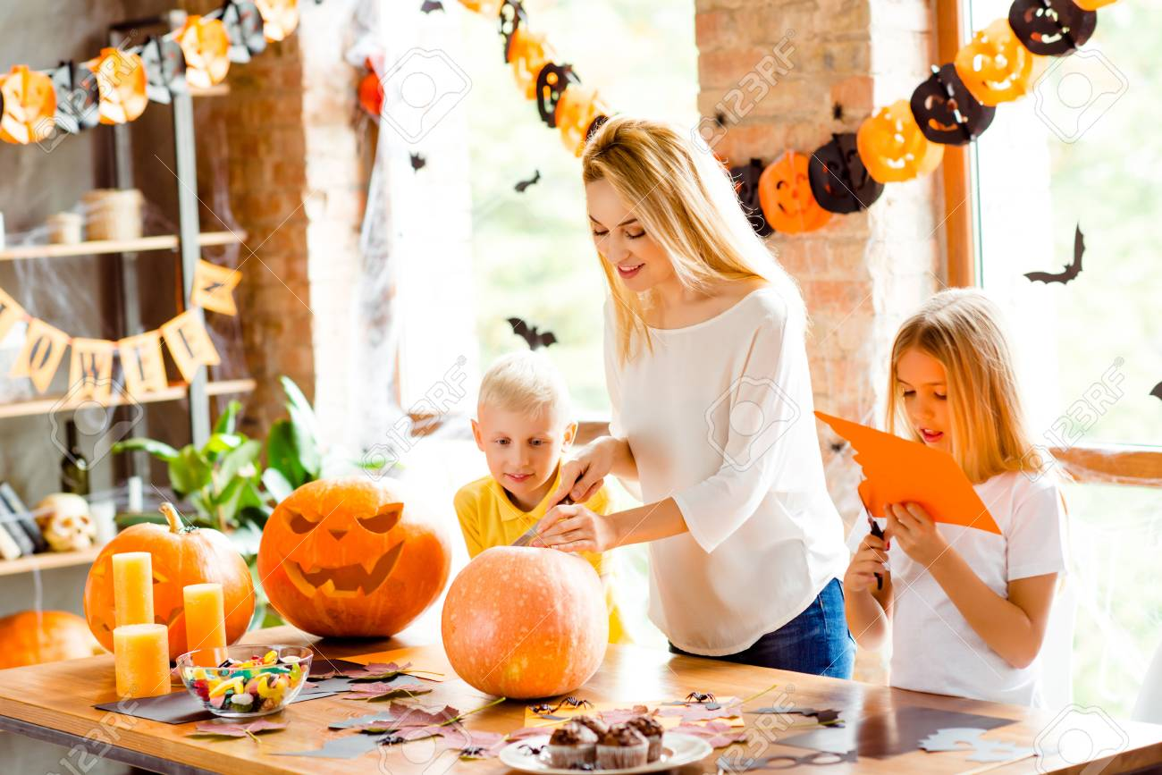 Halloween mood. Blonde family of mother and two siblings are preparing for party, cutting decorations, making jackolantern, desktop with candles, candies, fall leaves, little black bats on windows - 87389217