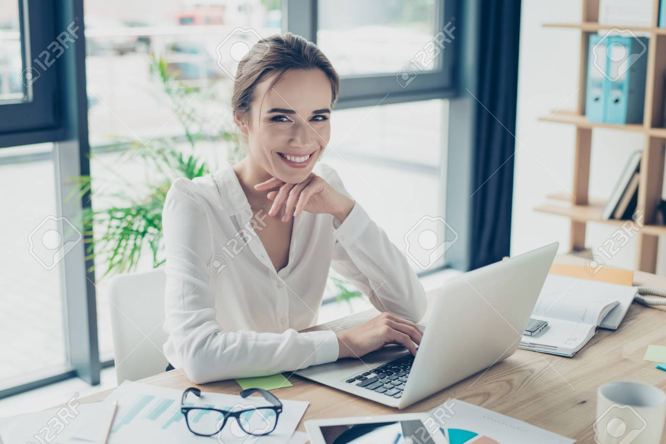 Development, authority, feminity concept. Pretty business woman is sitting at her light modern work station, checking e mails in front of digital device, smiling and looking at camera - 87597921