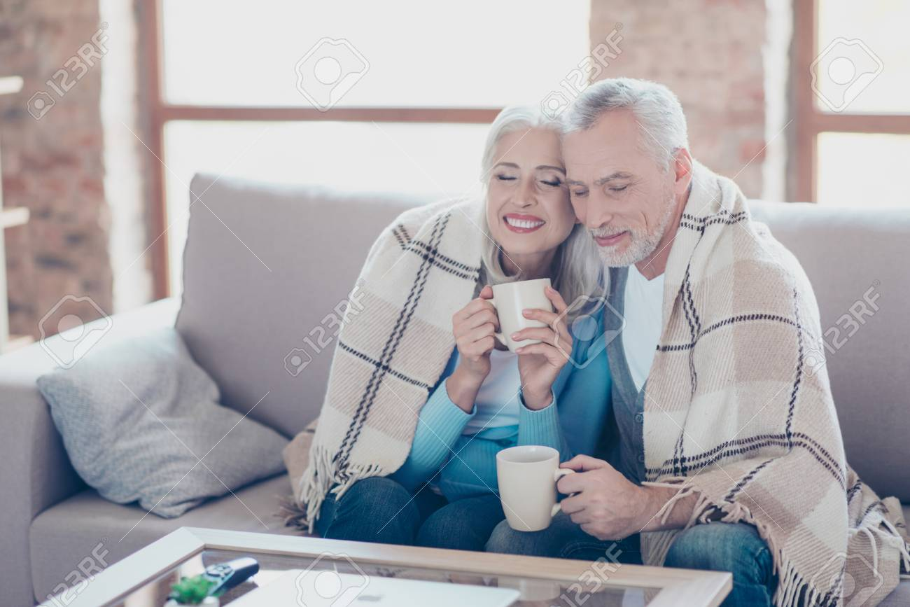 It is almost winter, so cold outside, but so sweet time we spend together! Happy cheerful peaceful couple of pensioners are resting, relaxing, hugging, drinking tea with closed eyes at the weekend - 90964346