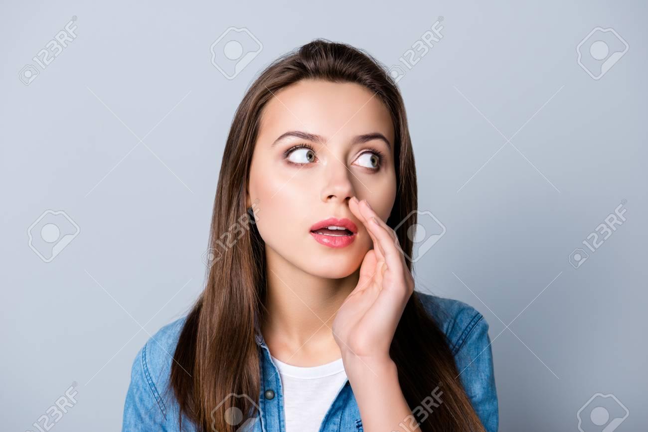 Close up portrait of cute beautiful gossip girl touching mouth