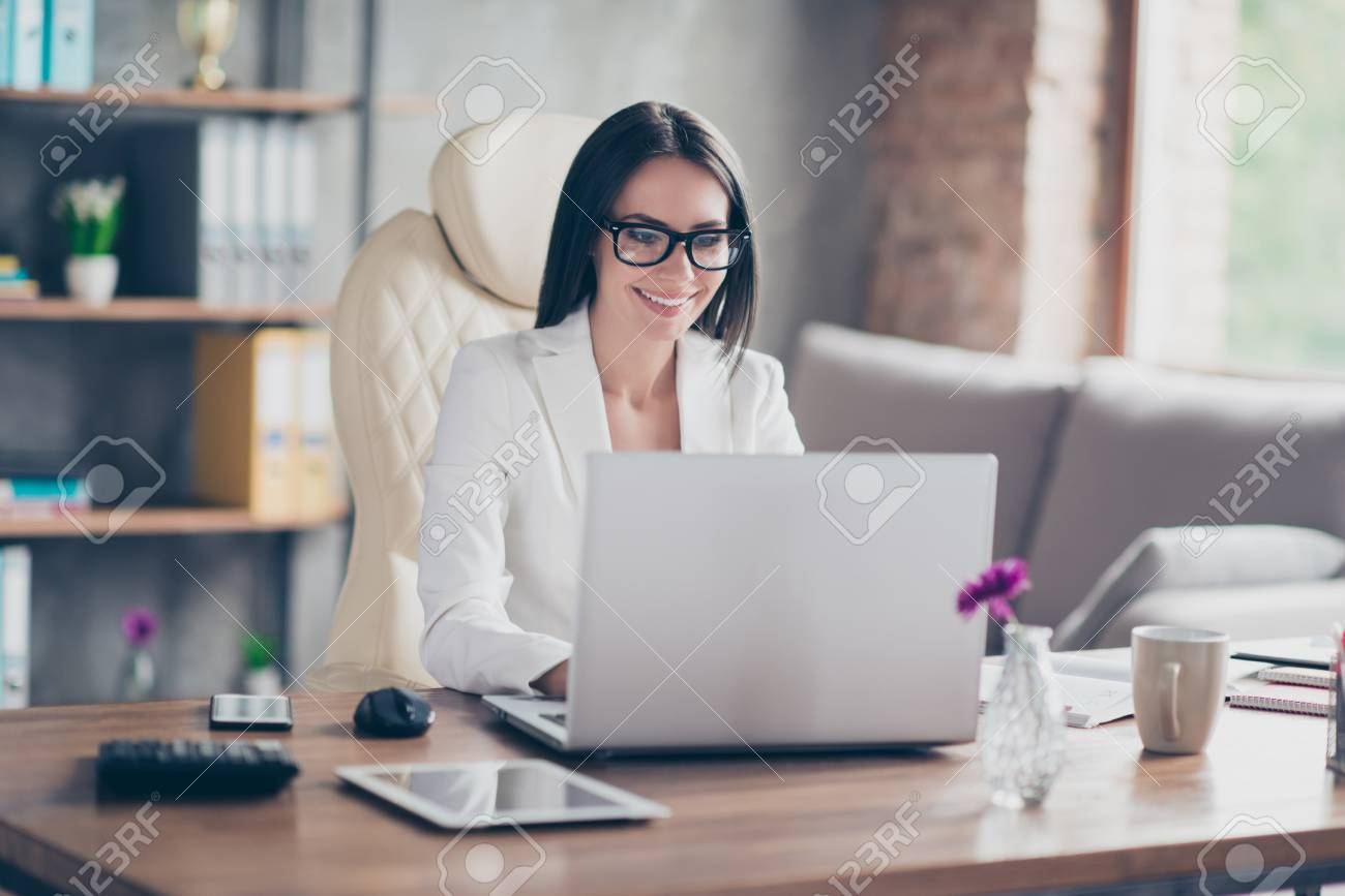 Beautiful confident smart stunning elegant journal editor is typing on laptop a new article for magazine, she is sitting at her workplace - 90964059