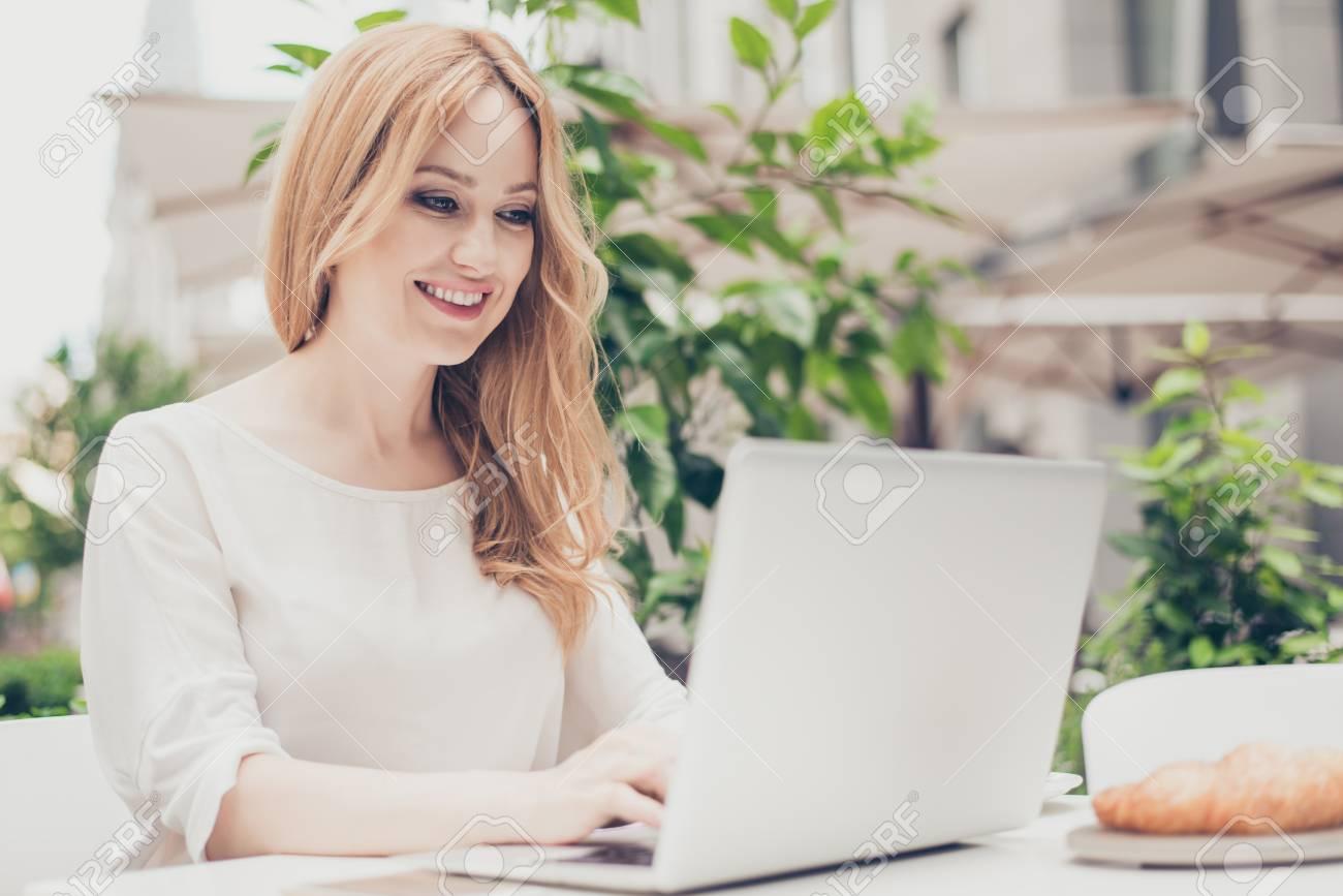 Pretty stylish woman working on computer outside - 91346562