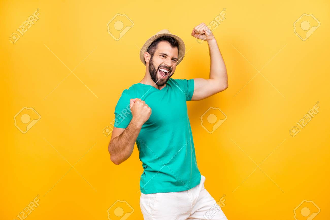 Happy excited cheerful joyous guy celebrating his victory with raised hands, isolated on yellow background - 91548487