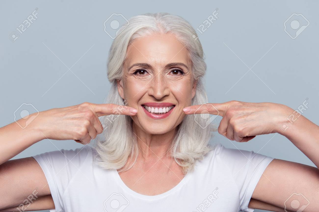 Concept of having strong healthy straight white teeth at old age. Close up portrait of happy with beaming smile female pensioner pointing on her perfect clear white teeth, isolated on gray background - 91651657
