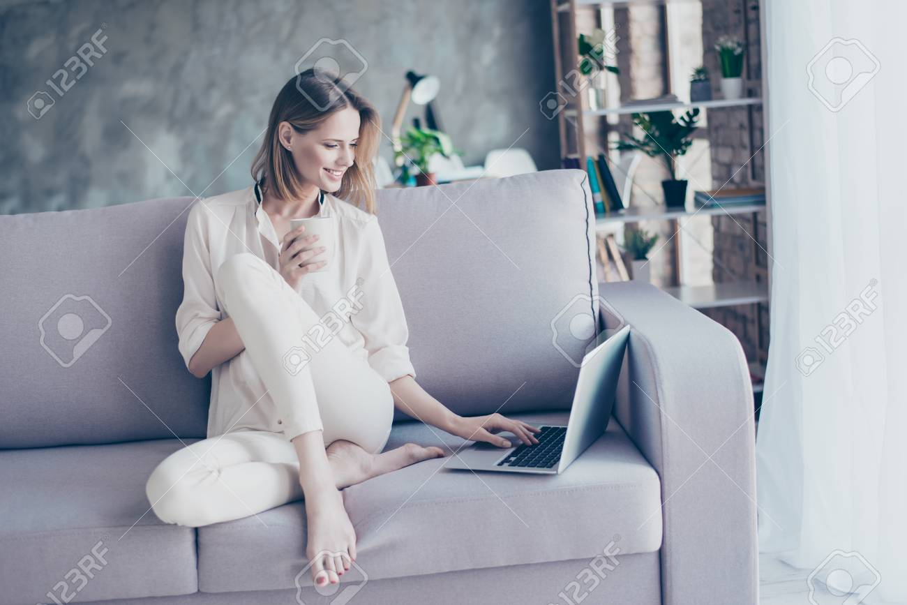 Beautiful smiling blonde woman sitting on couch using wi fi internet on her laptop for online shopping holding cup of tea - 91652461