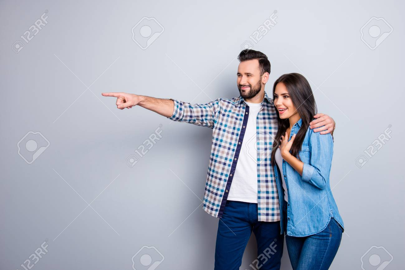 Bearded, smiling man embracing his excited, charming girlfriend and showing to her something with forefinger over grey background - 92490981