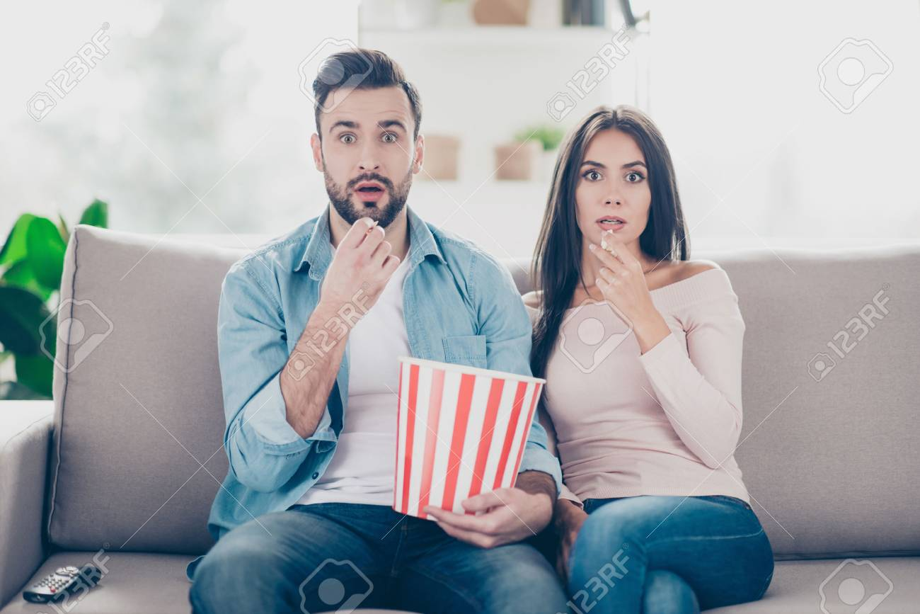 Unexpected turn of events in a film! Two charming beautiful funny man with bristle clothed in jeans denim outfit and attractive dressed in sweater and jeans woman are pop-eyes surprised watching tv - 93377134