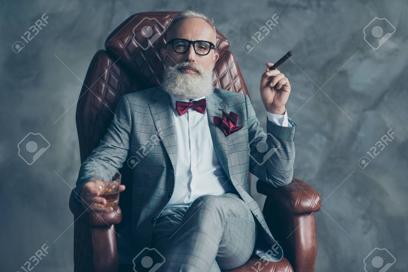 Cool man in glasses, hold cigarette, glass with brandy, in formal wear, tux with red bowtie and pocket square, sit in leather chair over gray background, looking to the camera, shares, stock, money - 93601668