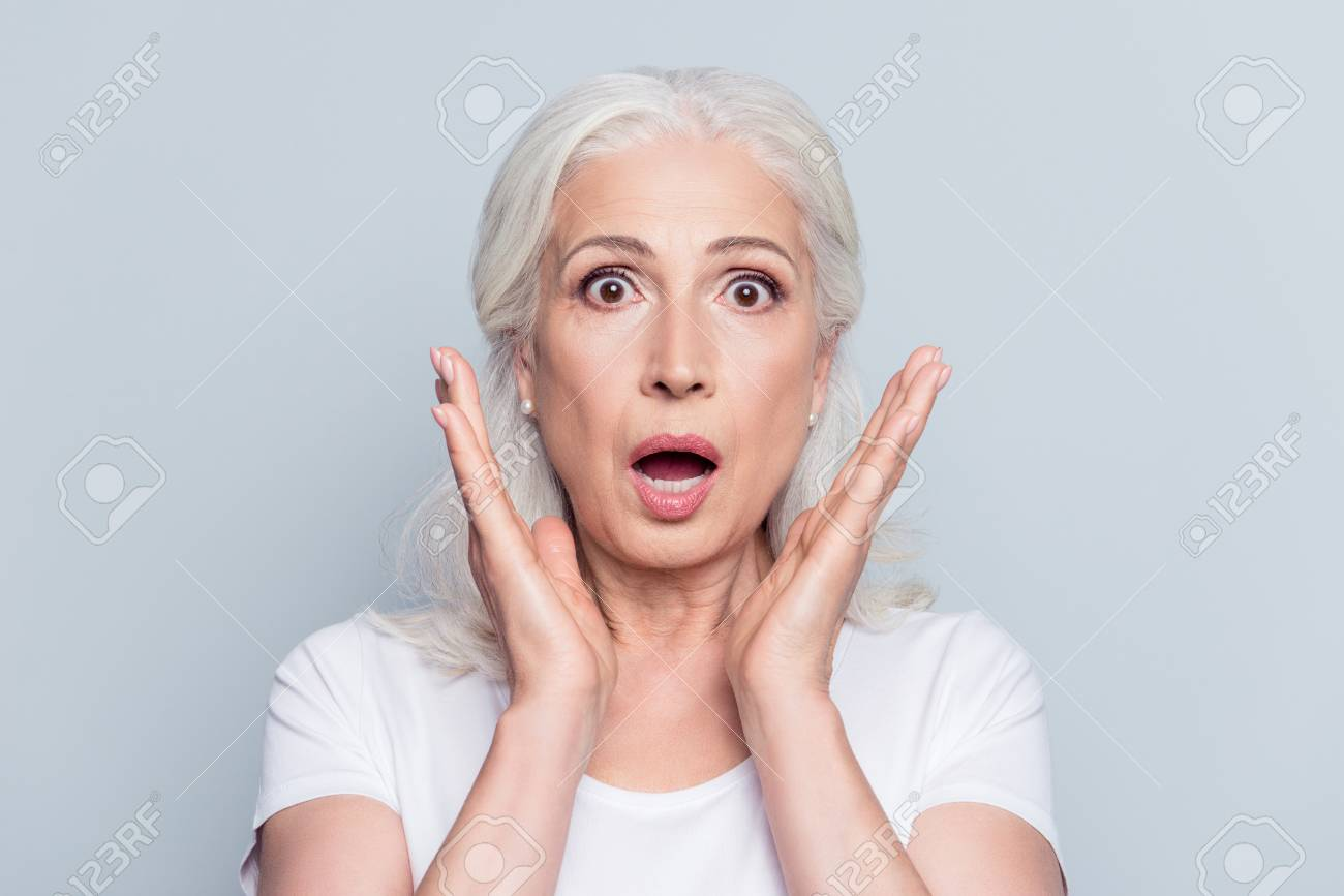 Pretty, nice, old, shocked, scared woman with wide open eyes and mouth in t-shirt holding palms near cheeks looking at camera over gray background - 95427481