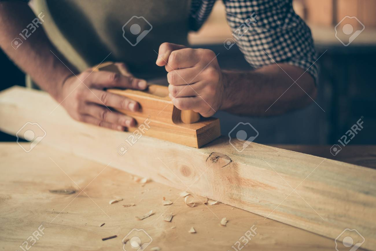 Cropped close up photo of handicraftsman's hands making a wooden plank smooth and without thorns, he is holding a plank - 97559843