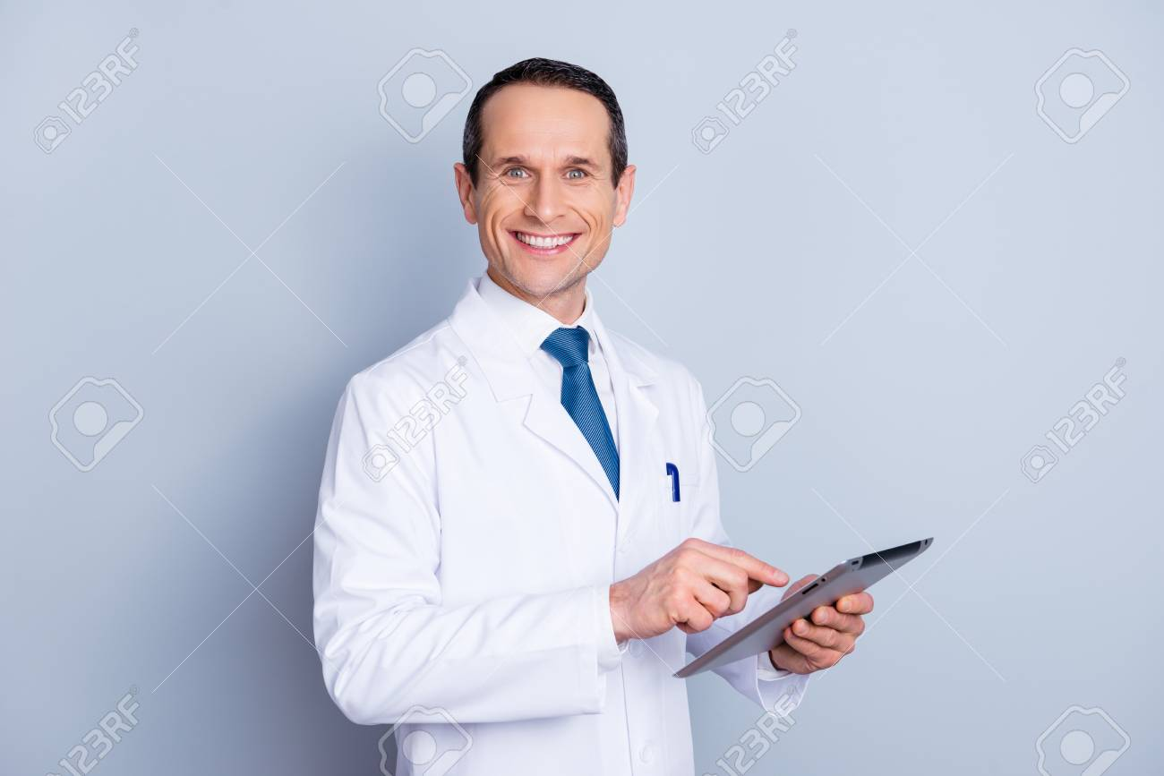Portrait of cheerful glad gifted smart with toothy smile doctor using modern pad at work isolated on gray background copy-space - 97864772