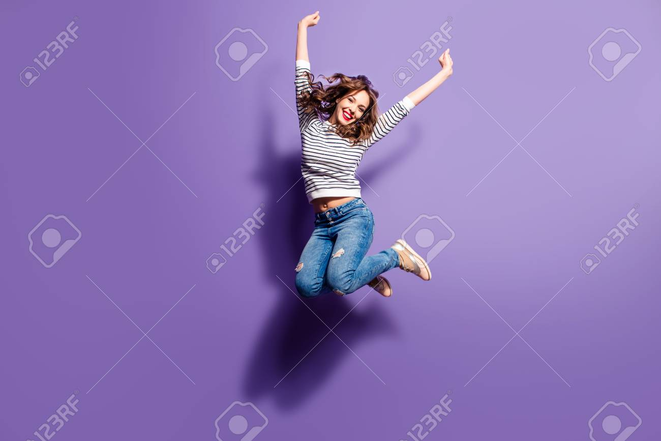 Portrait of cheerful positive girl jumping in the air with raised fists looking at camera isolated on violet background. Life people energy concept - 104366506