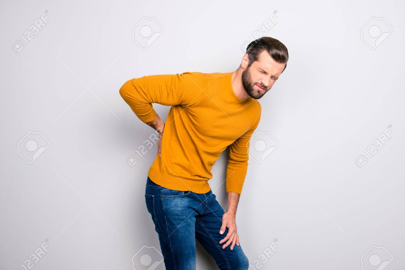 Side profile half-turned portrait of grimacing sad upset unhappy with serious pain in back man wearing yellow tight sweater and jeans isolated on gray background copy-space - 105714036