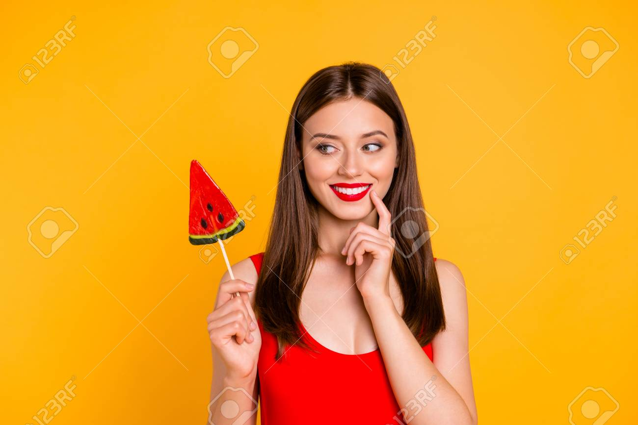 To be or not to be? Close up portrait happy and cute young woman holding piece on caramel fruit on stick, looking thoughtfully aside isolated on bright yellow background - 106119554