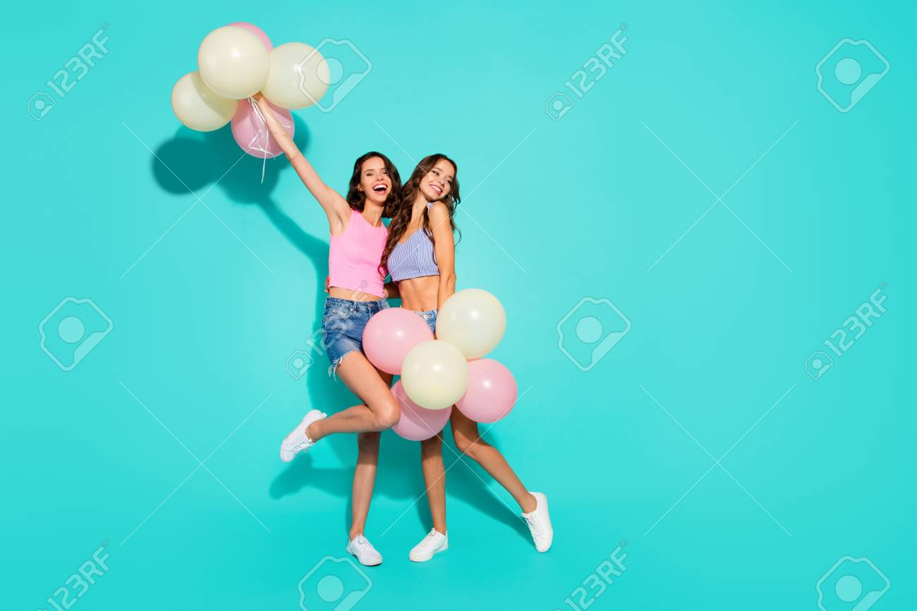 Full length body size photo funny beautiful amazing two she her ladies colored balloons hands arms raised skinny legs wearing shiny jeans denim shorts tank tops isolated teal bright vivid background - 117001081