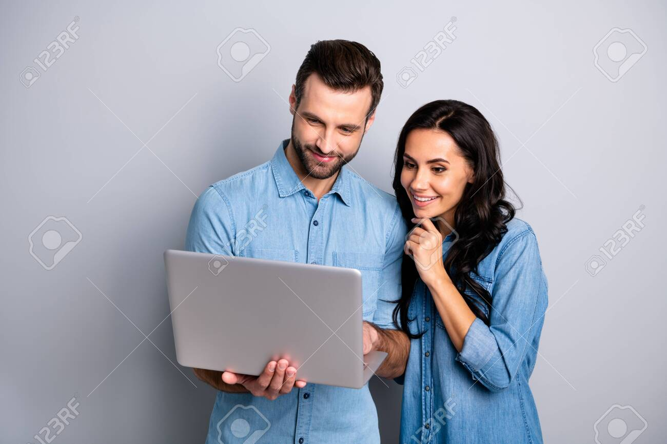Portrait of charming inspired students using electronic devices watching videos browsing sites social networks isolated dressed in blue denim clothing on gray background - 119455104