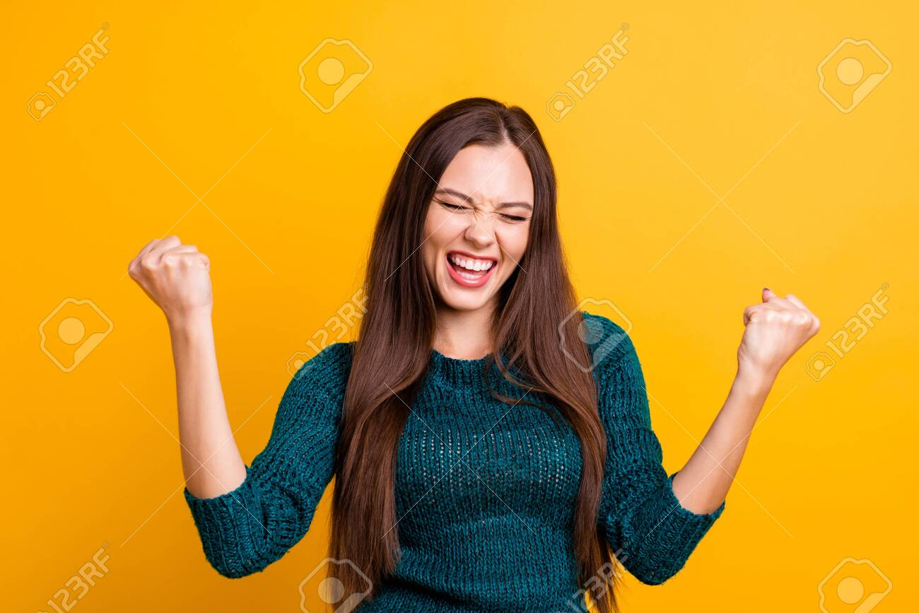 Close up photo beautiful yelling her she lady eyes closed open toothy mouth arms fists raised up air brown eyes ecstatic wear green knitted pullover jumper clothes isolated yellow background - 121963035