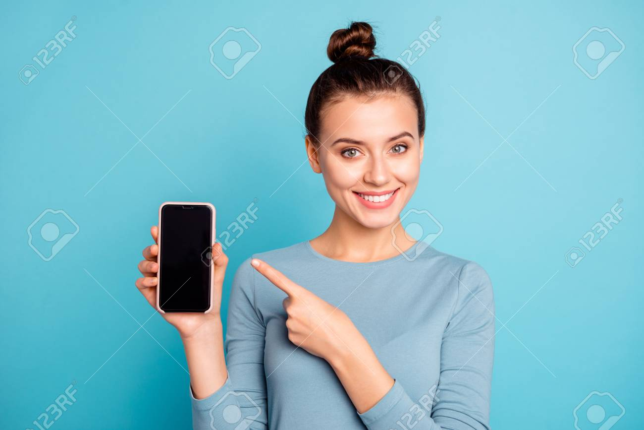 Close-up portrait of her she nice-looking attractive sweet lovely cheerful teenage girl holding in hand new cool buying purchase ad advert isolated over bright vivid shine turquoise background - 121967016