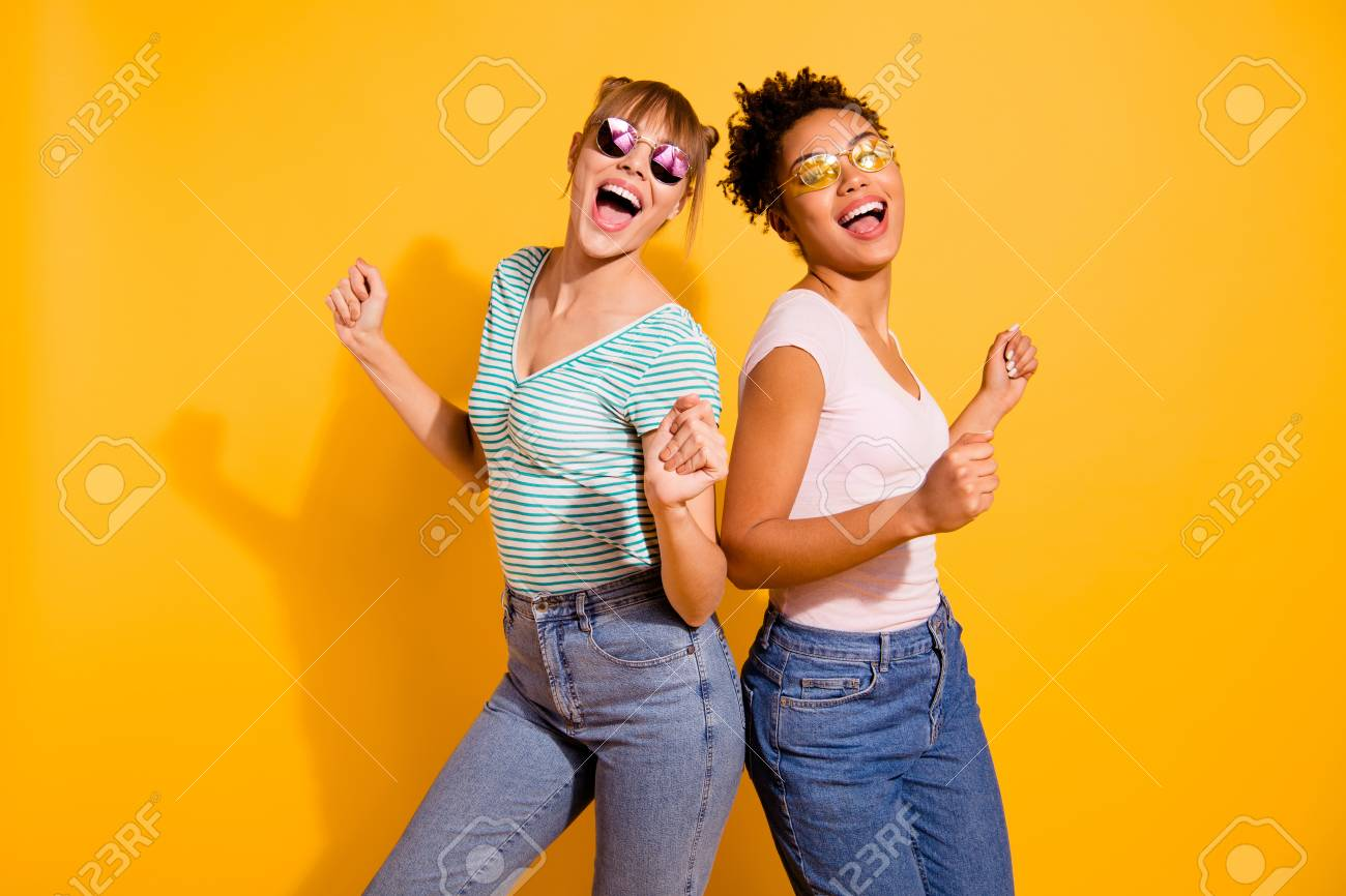 Close up photo beautiful funny she her lady party guys hands arms raised up modern motion different nationalities wear sun specs casual white striped t-shirt clothes isolated yellow bright background - 123700815
