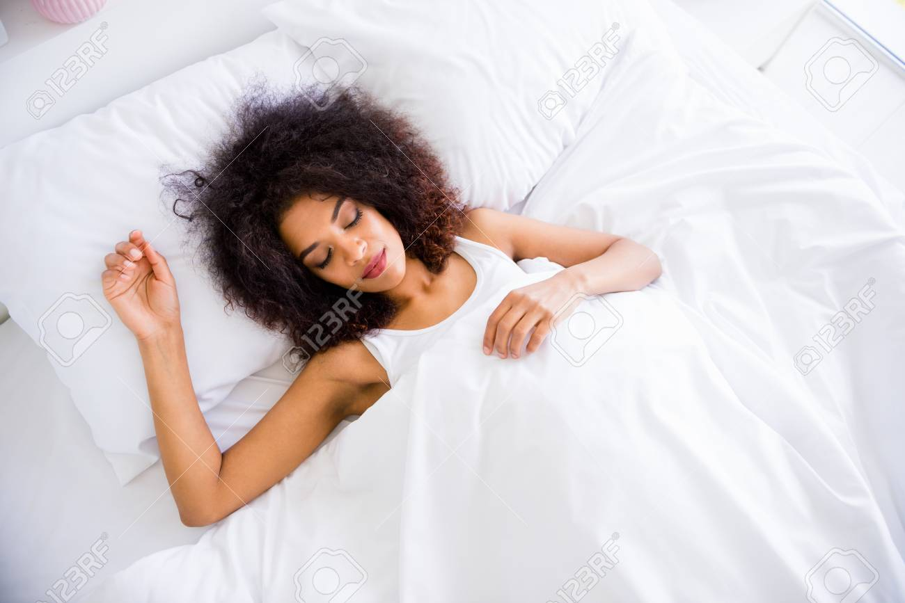 Close up top above high angle view photo beautiful she her dark skin lady vacation wakeup healthy dreaming eyes closed saturday white sheets sleep wear lying comfort large bedroom house indoors - 123849917