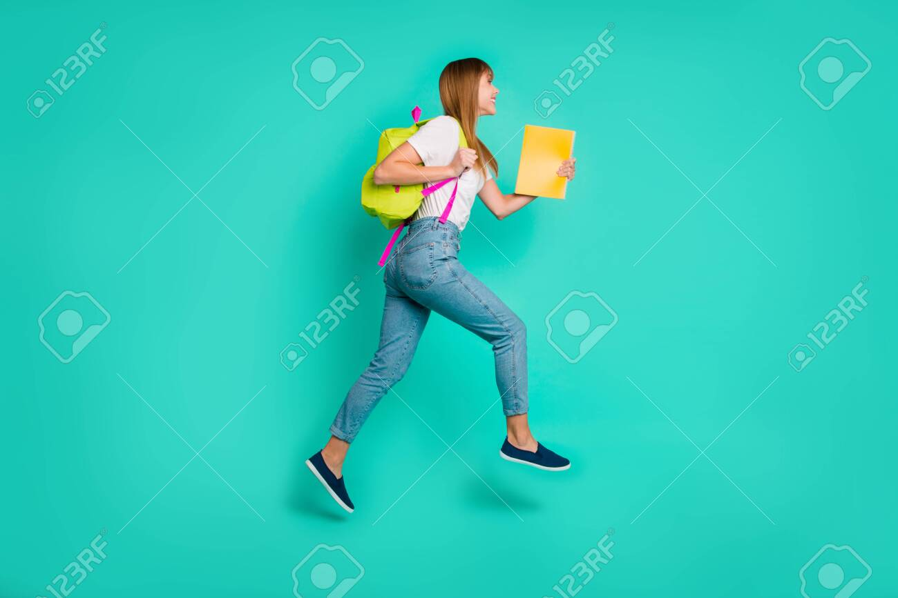 Full length side profile body size photo beautiful she her lady jump high arms hands hold back pack notebooks on way school friendly wear specs casual white t-shirt isolated teal green background - 123919717