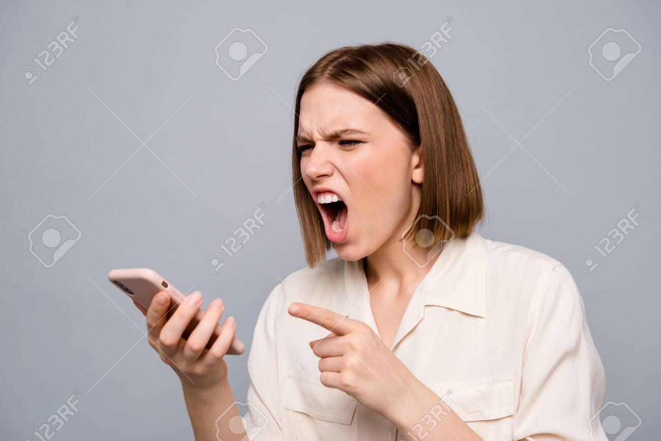 Close up photo furious amazing beautiful she her lady hold hands arms telephone listen unexpected bad news wild roar boyfriend displeased madness wear casual white shirt isolated grey background - 127056356