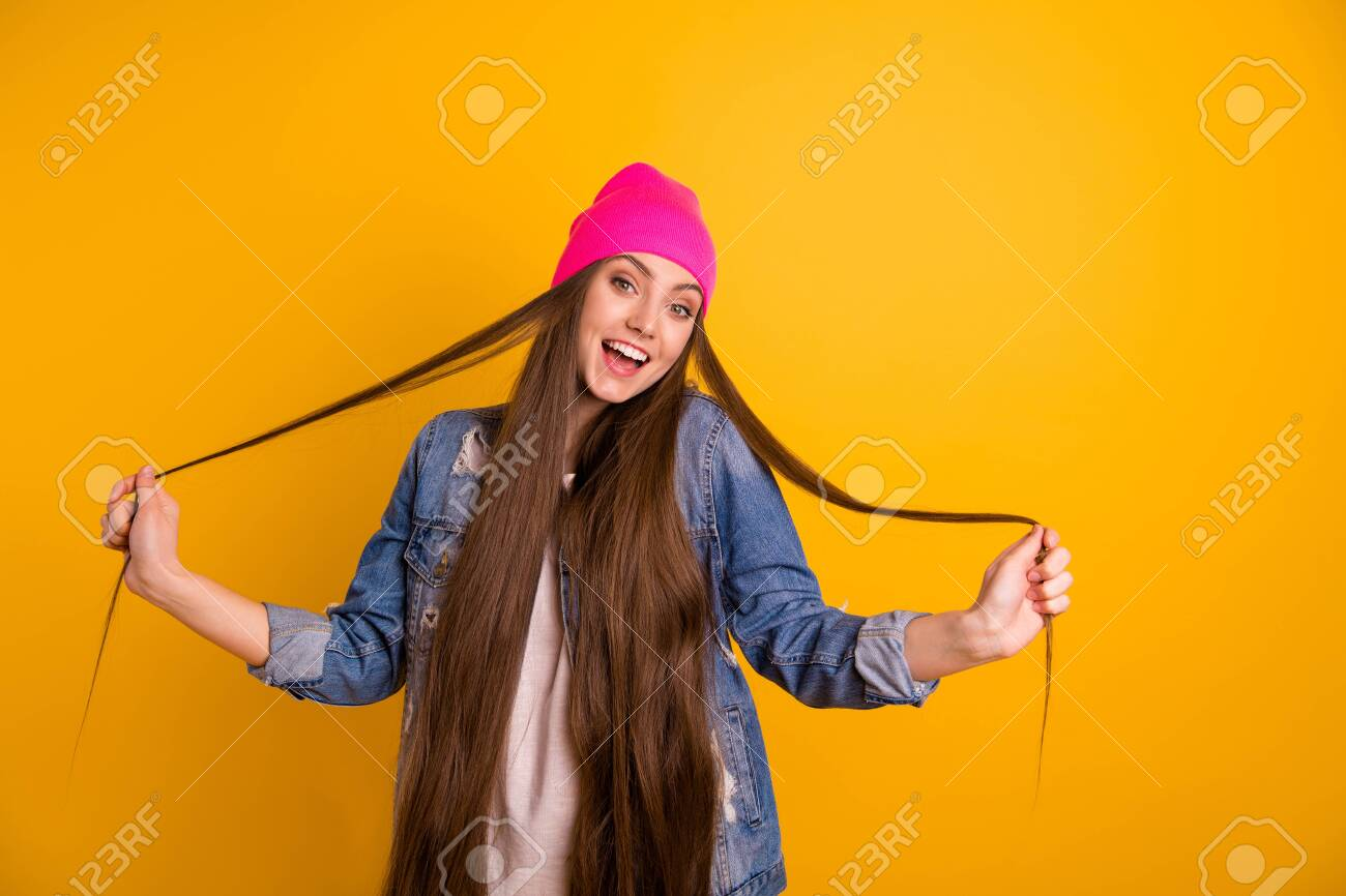 Close up photo beautiful amazing she her stylish lady friendly teen playing very long curls weekend vacation day off mood wear casual jeans denim jacket pink hat isolated yellow background - 127233541