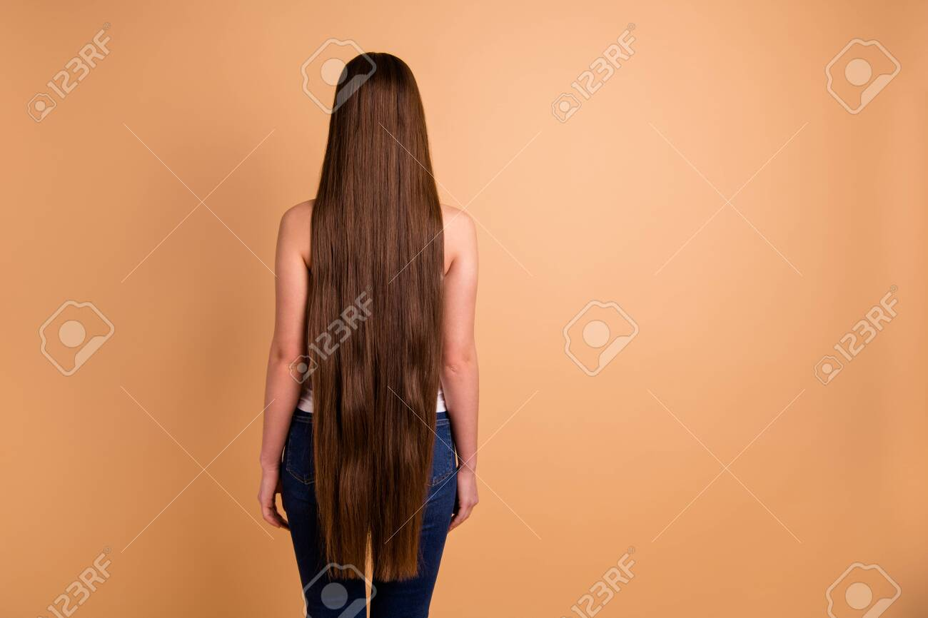 Close up back rear behind view photo beautiful amazing her she lady very long brown hair showing great condition every curl wear casual white tank-top jeans denim isolated pastel beige background - 127384557