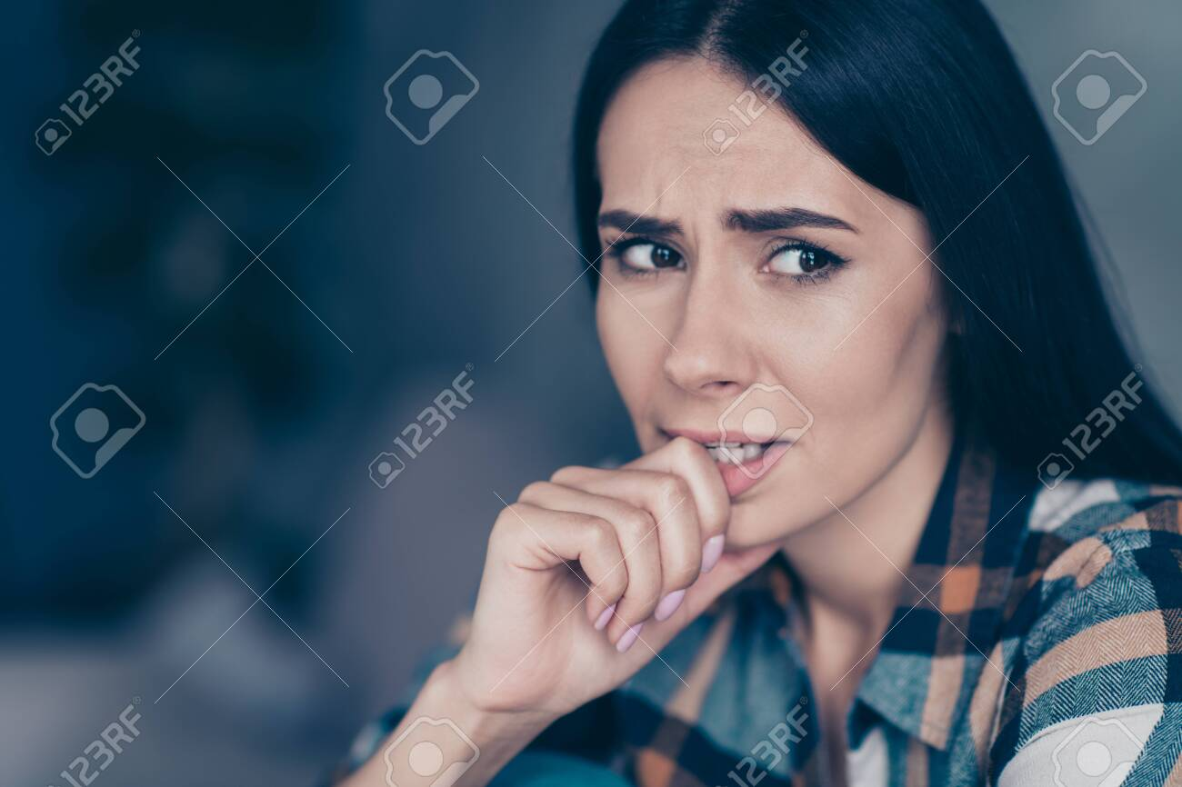 Close up side profile photo she her lady displeased hopeless arm hand bite fingers nerves made mistake have doubts tell or no wear checkered plaid shirt sit lean divan flat house living room indoors - 127523884