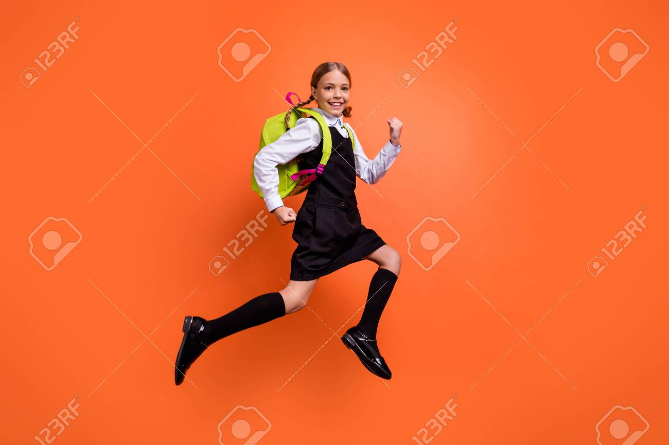 Full length body size view of nice attractive lovely cheerful cheery glad diligent pre-teen girl nerd running fast first grade back to school isolated on bright vivid shine orange background - 128451586