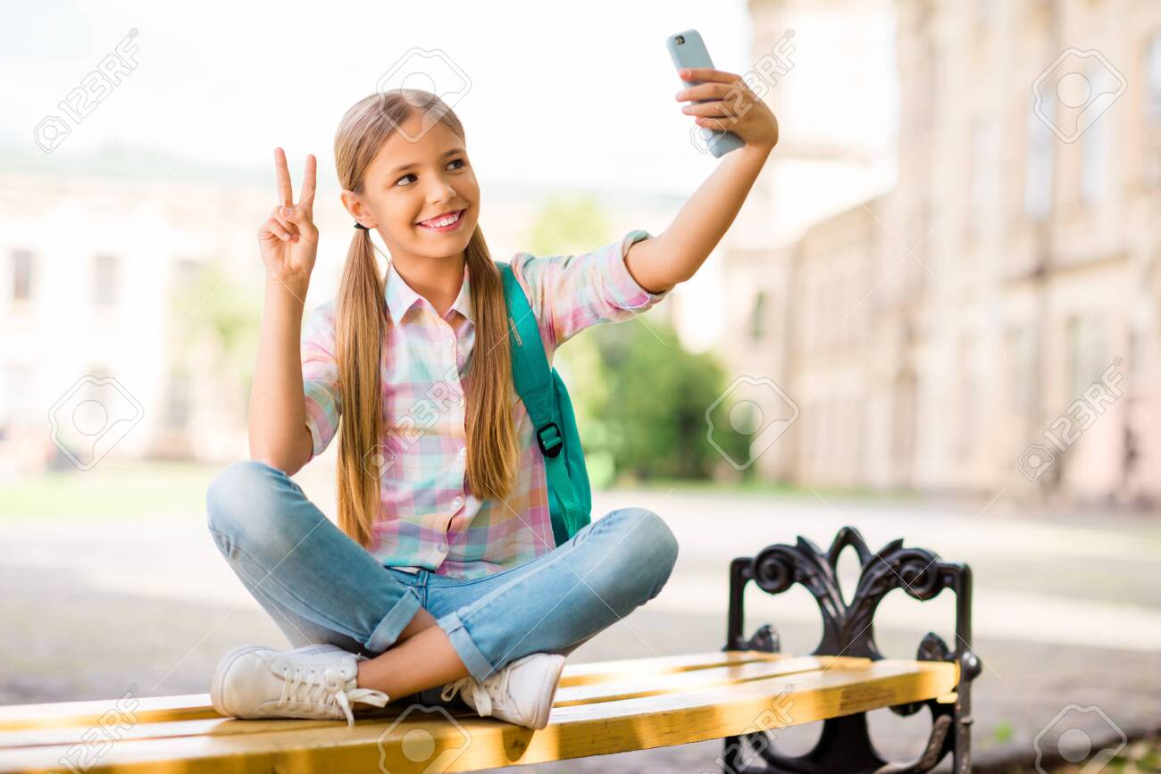Full body photo of cheerful student having pigtails ponytails make photo v-sign hold backpack rucksack wear plaid t-shirt denim jeans sit with folded legs - 129152849
