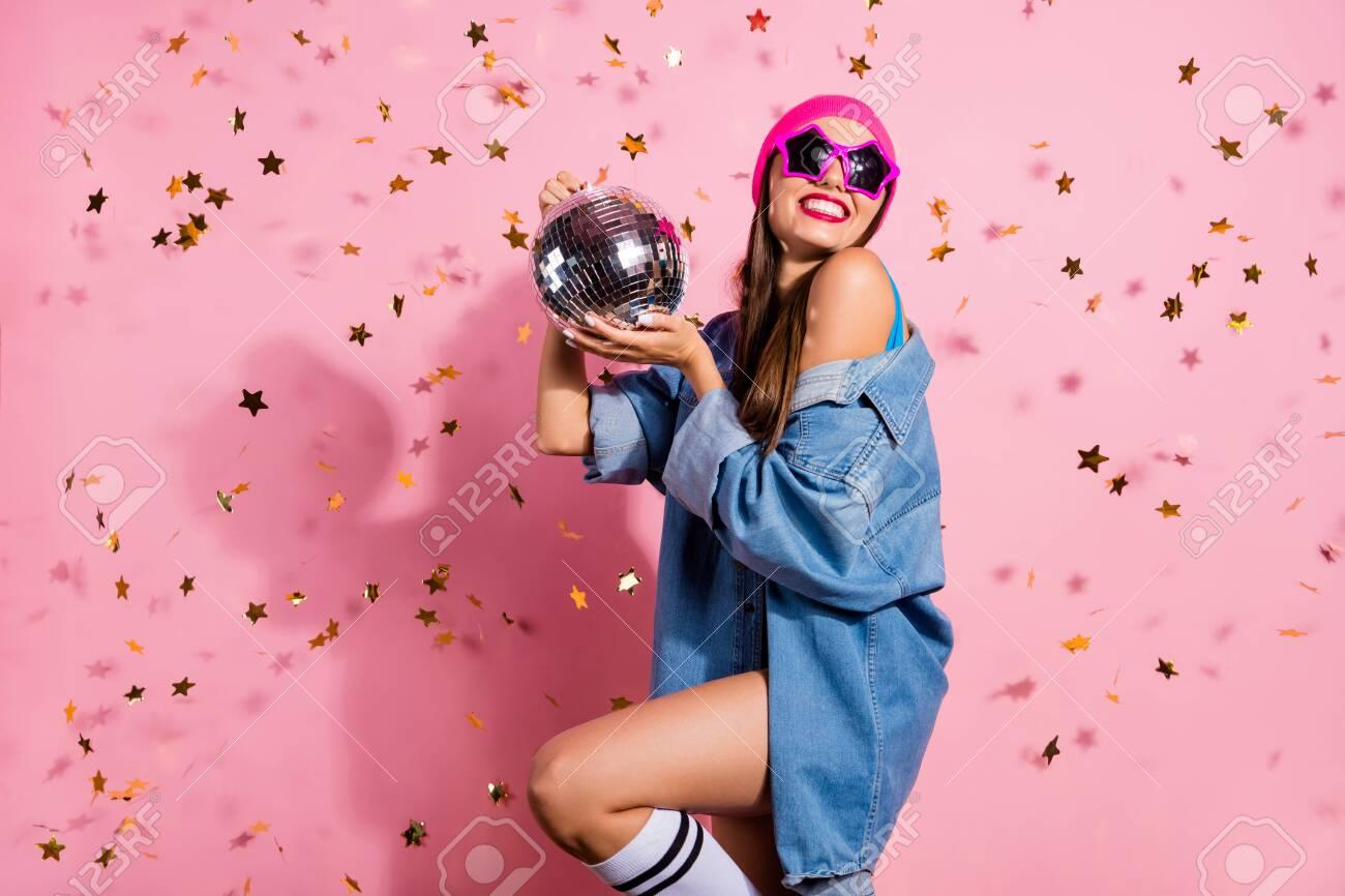 Portrait of elegant party youth holding mirror ball wearing denim jeans jacket eyewear eyeglasses isolated over pink background - 129185692