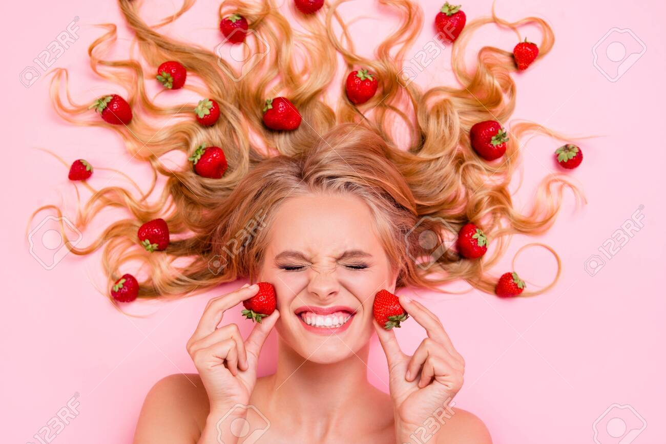 Close up top above high angle view photo beautiful she her lady lying down among fruit strawberries long hair strong action of facial fruit scrub mask cream moisturizer lotion isolated pink background - 130344031