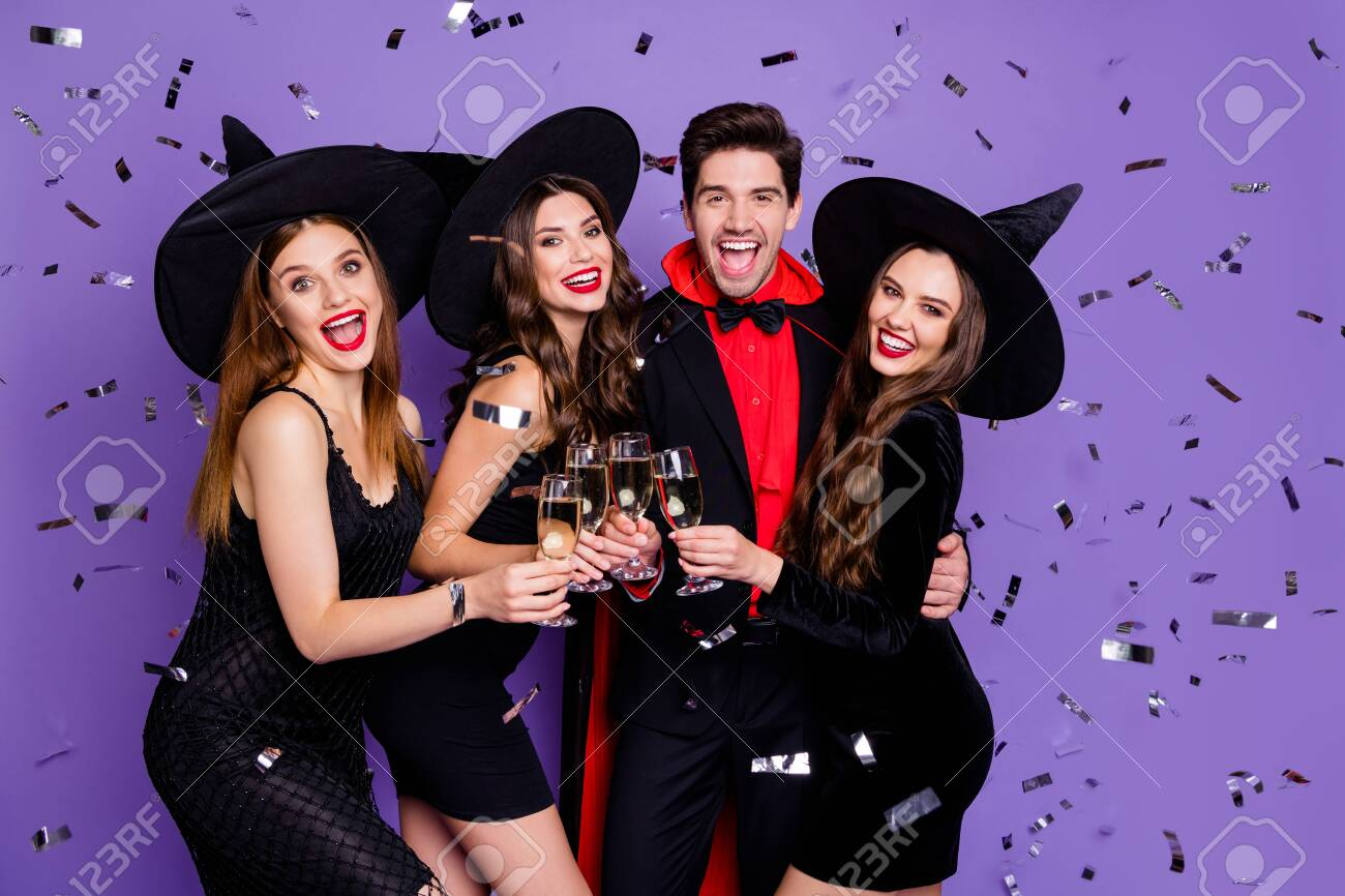 Photo of witch ladies and wizard guy at helloween event drink golden wine glitter flying in air wear black dresses caps suit and long coat isolated purple color background - 130343381