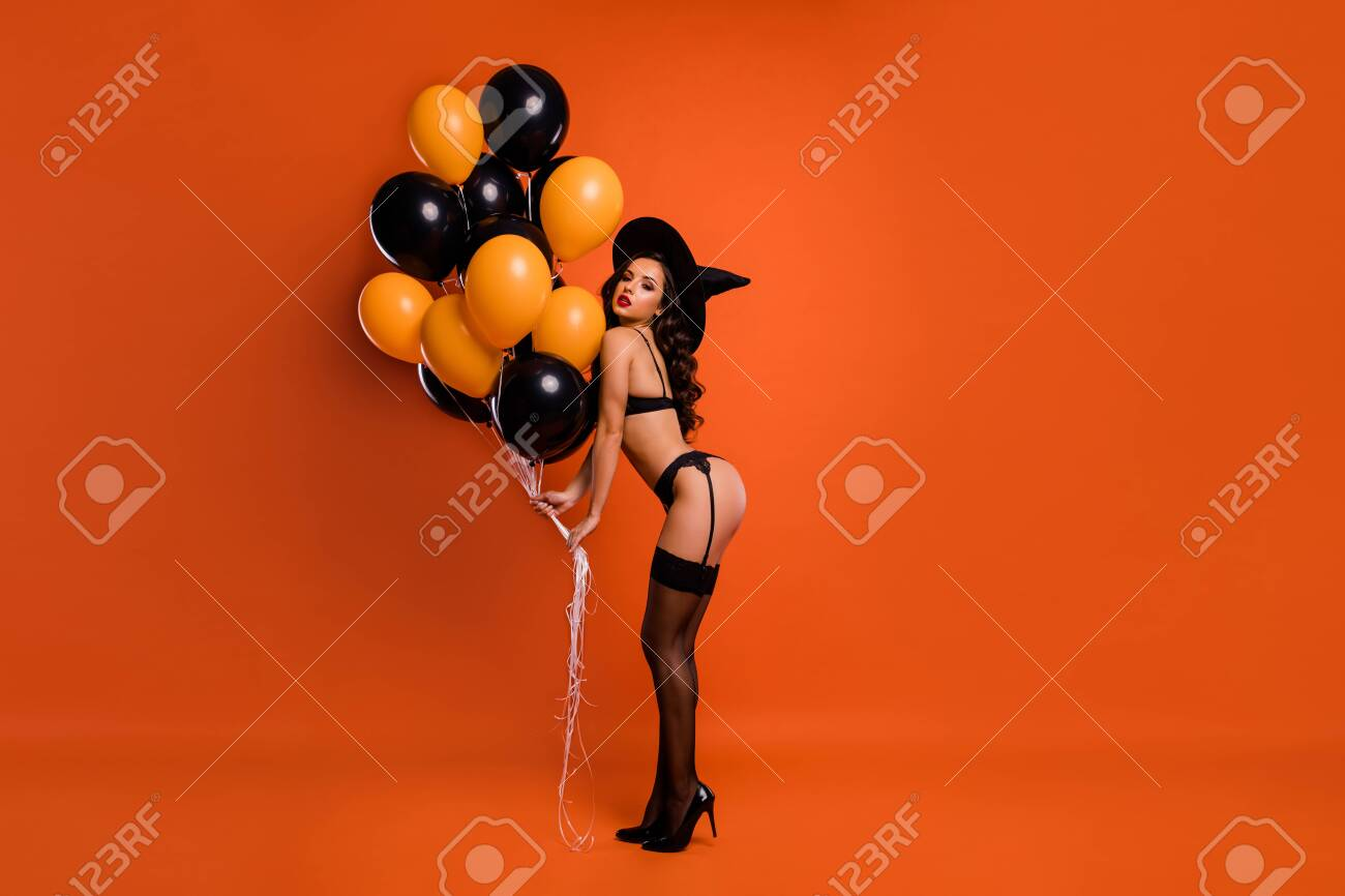 Full size photo of beautiful lady hold air balloons make private party showing husband ideal figure wear black bikini tights witch cap isolated orange background - 130571933