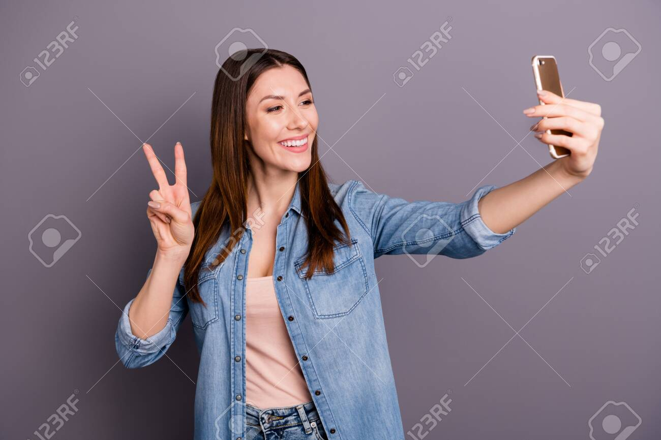 Portrait of positive cheerful woman take selfie on her cellphone have video call feel content make v-signs on her vacation holidays, wear denim jeans clothes isolated over grey color background - 147528030