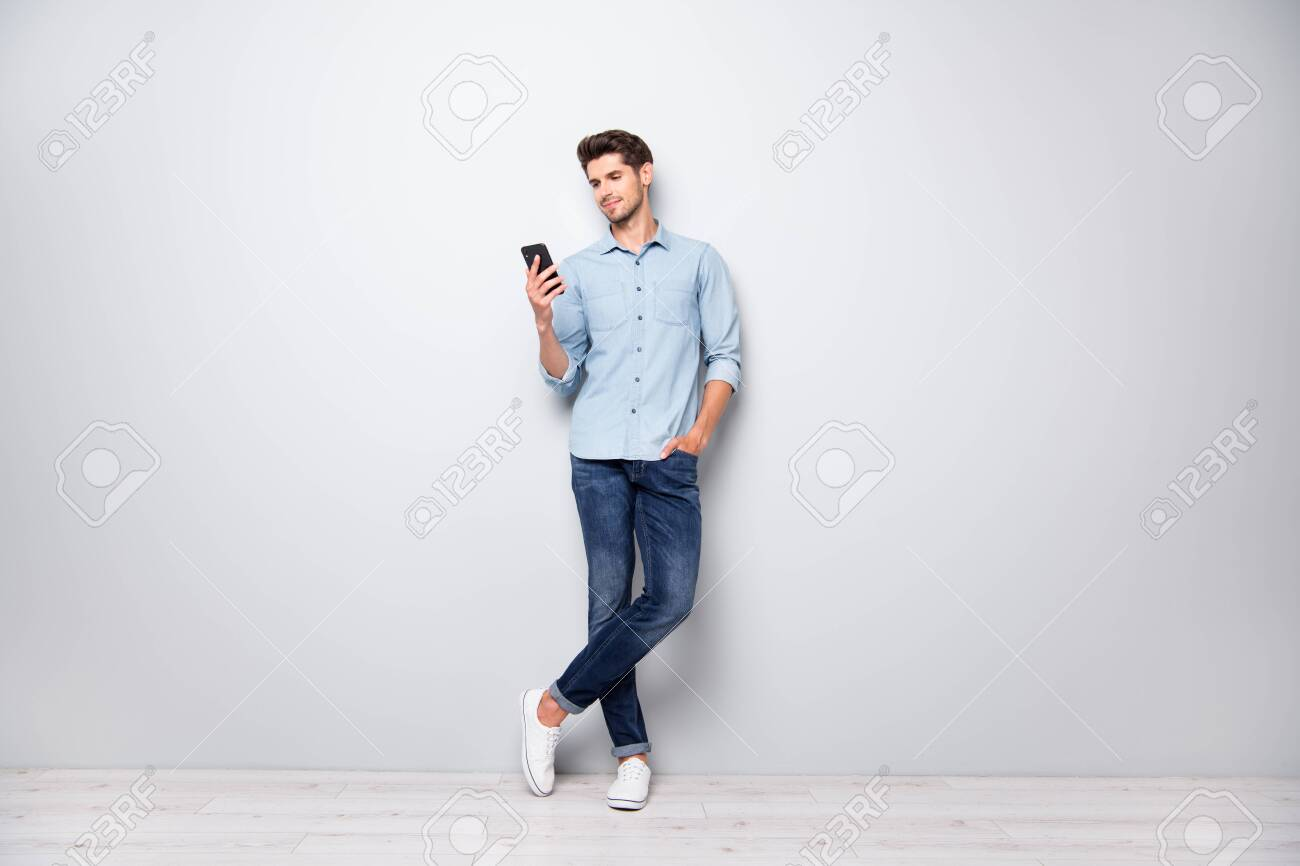 Full size photo of concentrated smm worker man use cellphone answer sms messages have online conversation with friends type comments posts wear stylish outfit sneakers isolated grey color background - 132532197