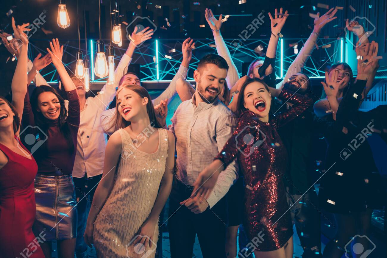 Photo of dancing people dressed in formalwear rejoicing good free time together with macho surrounded by girls hanging out between them in falling confetti - 133115901