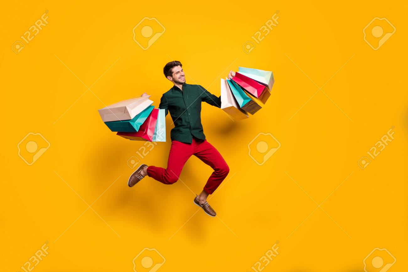 Full length body size photo of cheerful positive handsome jumping man holding numerous packages returning from shopping mall isolated vivid color background - 133739954