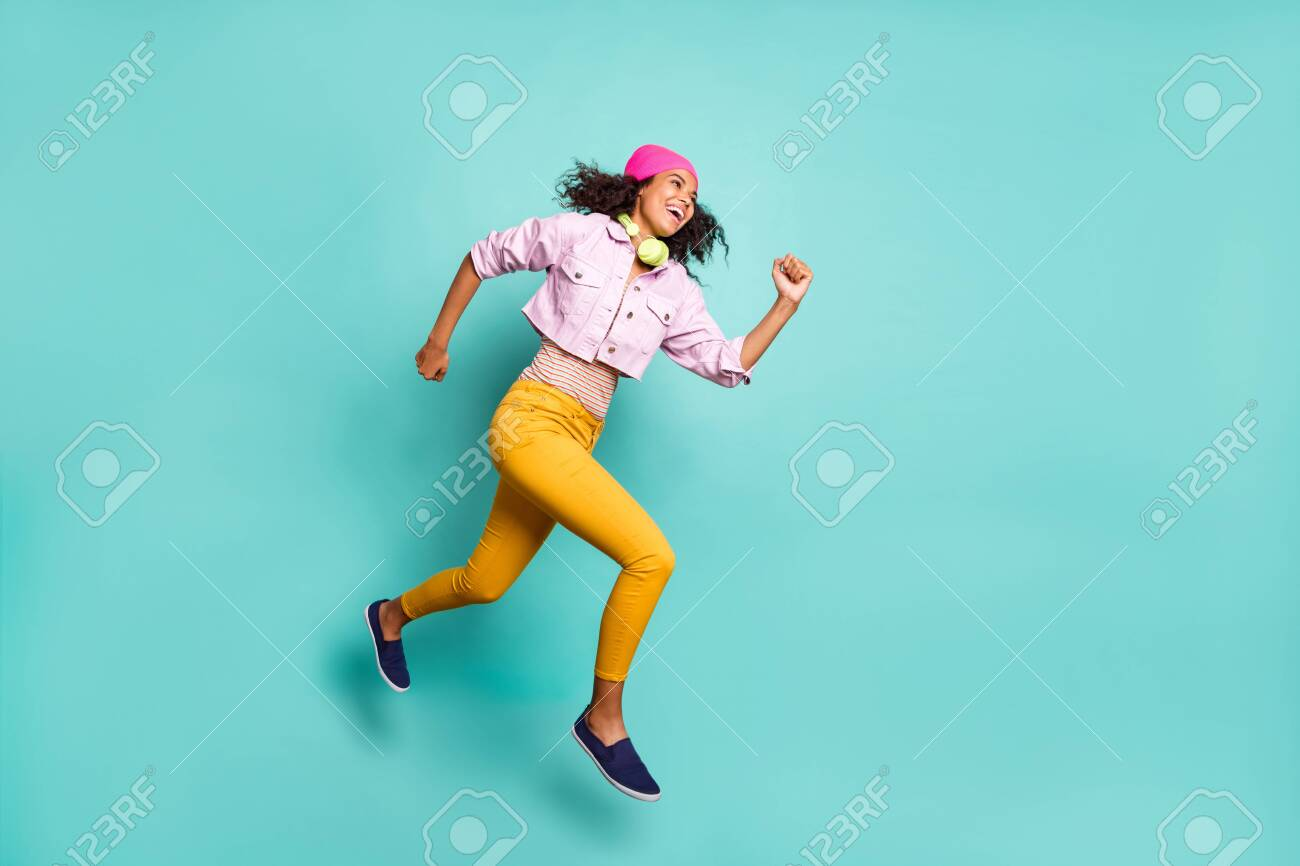 Turned full length body size photo of casual positive running jumping girl aspiring for discounted goods wearing yellow pants trousers pink jacket striped t-shirt isolated teal color background vivid - 133956688