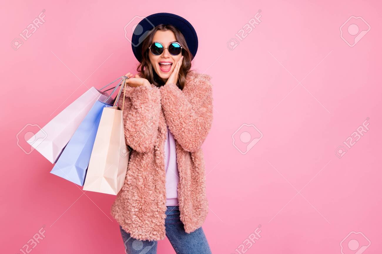 Photo of pretty lady hold carry many packs shopper tourism abroad look unbelievable sale prices hand on cheek store wear jacket sun specs hat jeans isolated pink background - 133956964