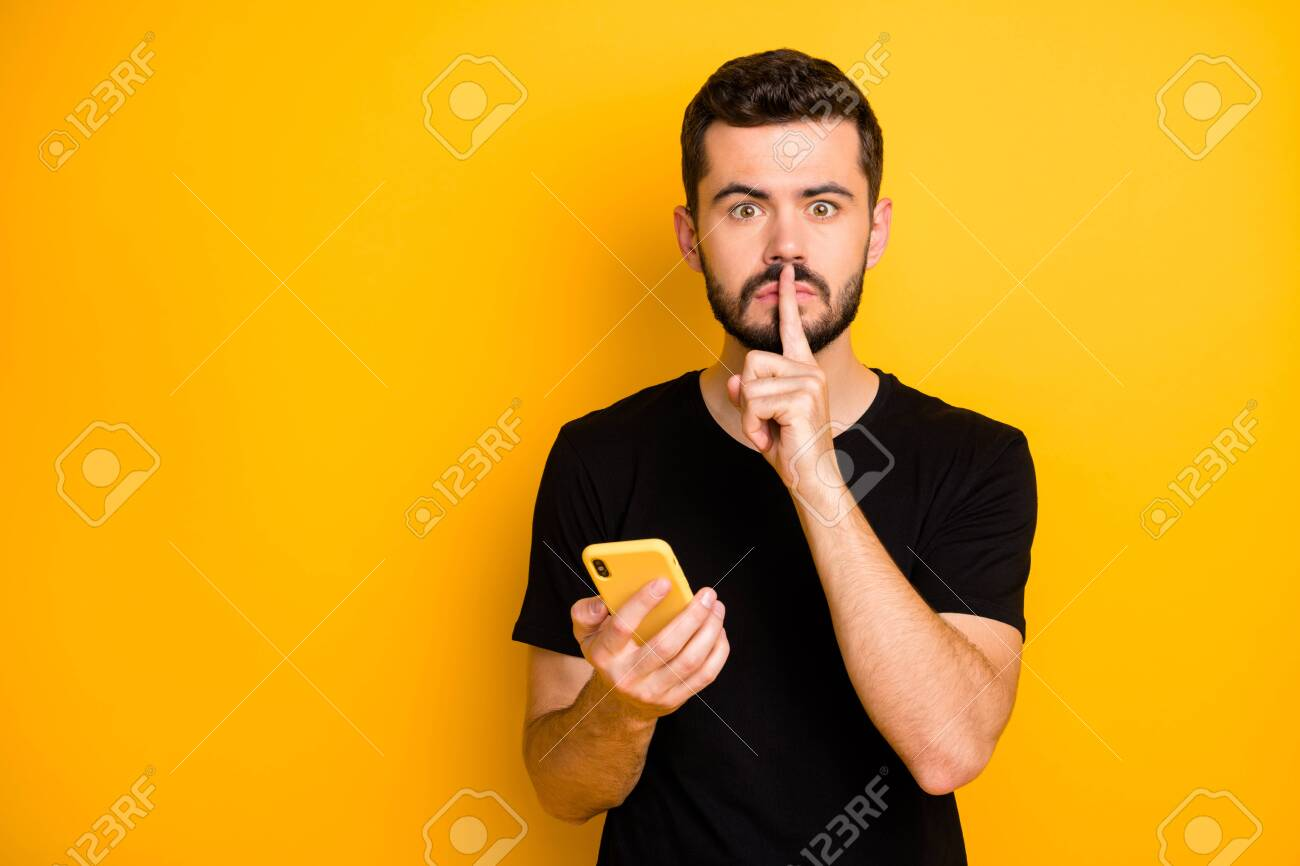 Censorship no telling secret concept. Serious guy blogger hold use cellphone search private fake news show mute quiet sign index finger wear black t-shirt isolated yellow color background - 134530812