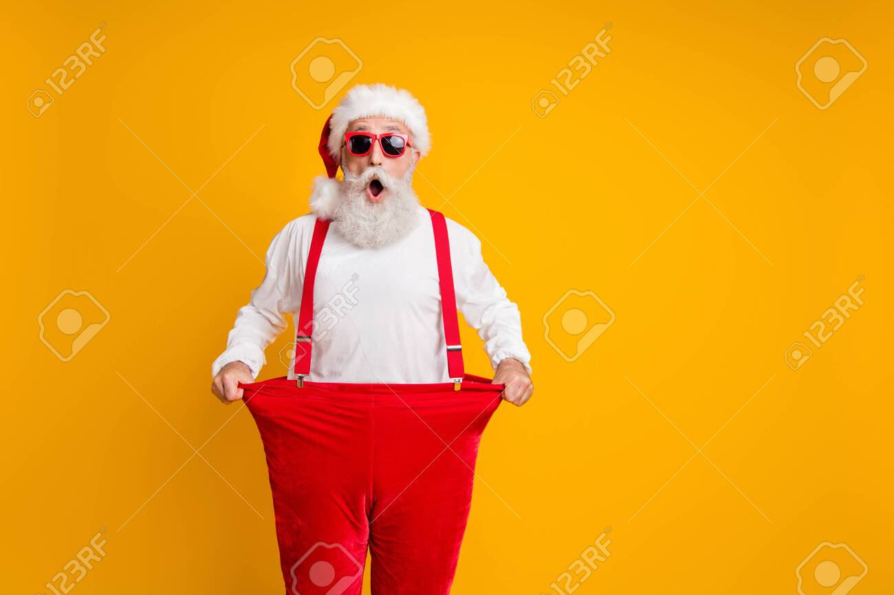 Portrait of crazy funky white bearded grandfather in santa claus hat hold big size trousers lose weight belly x-mas time show dieting effect isolated yellow color background - 134369455