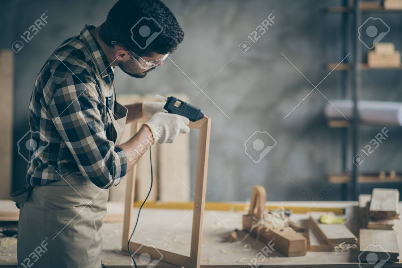 Profile side photo of serious concentrated worker man use electric hot glue gun to repair wooden construction frame work in home house garage - 134707793