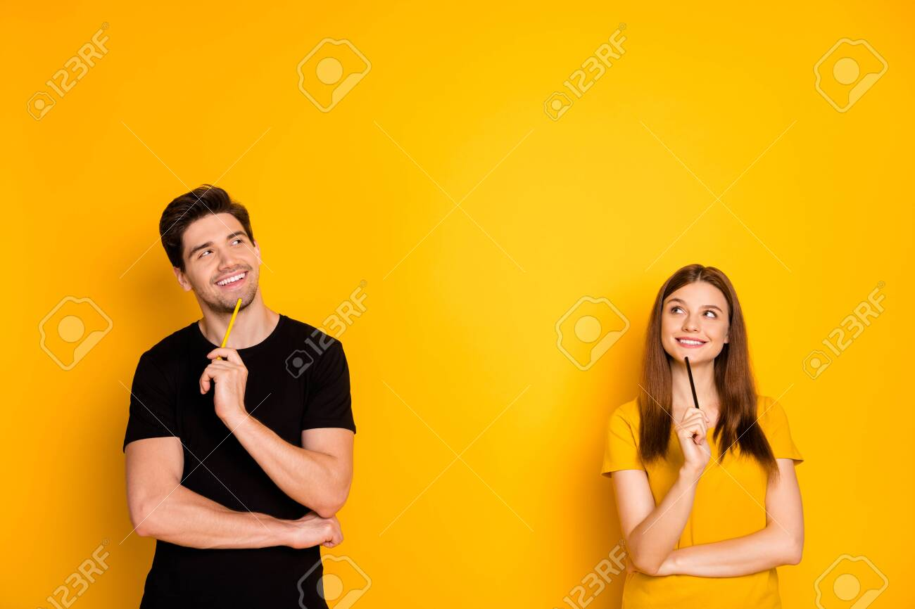 Photo of cheerful positive cute nice charming pretty couple holding pens wearing black t-shirt smiling toothily looking into empty space a fit of thoughts isolated over bright shiny color background - 134708107