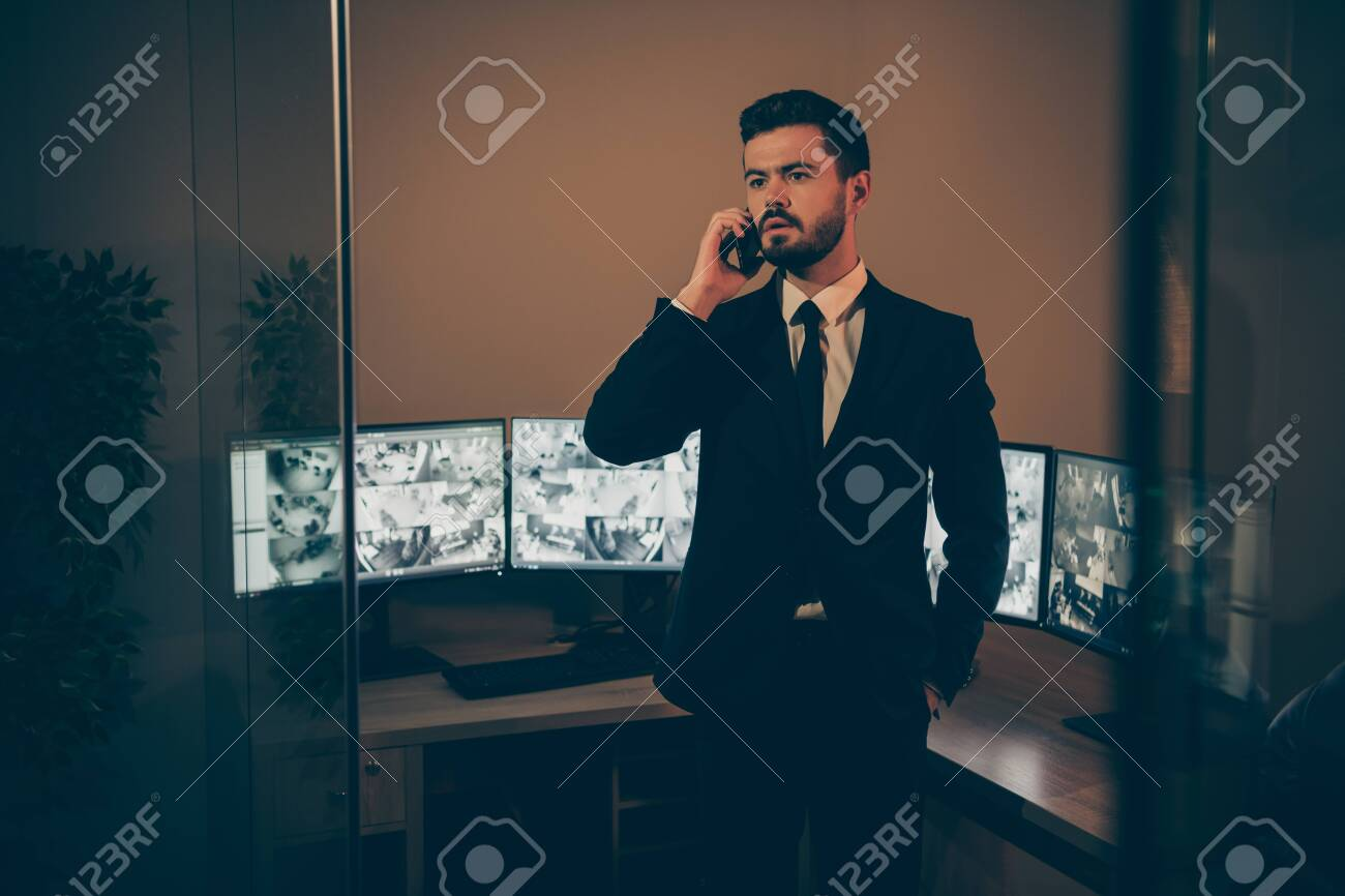 Portrait of his he nice attractive serious professional experienced stylish imposing man supervising online remote panel night shift talking to partner at work place station - 135269215