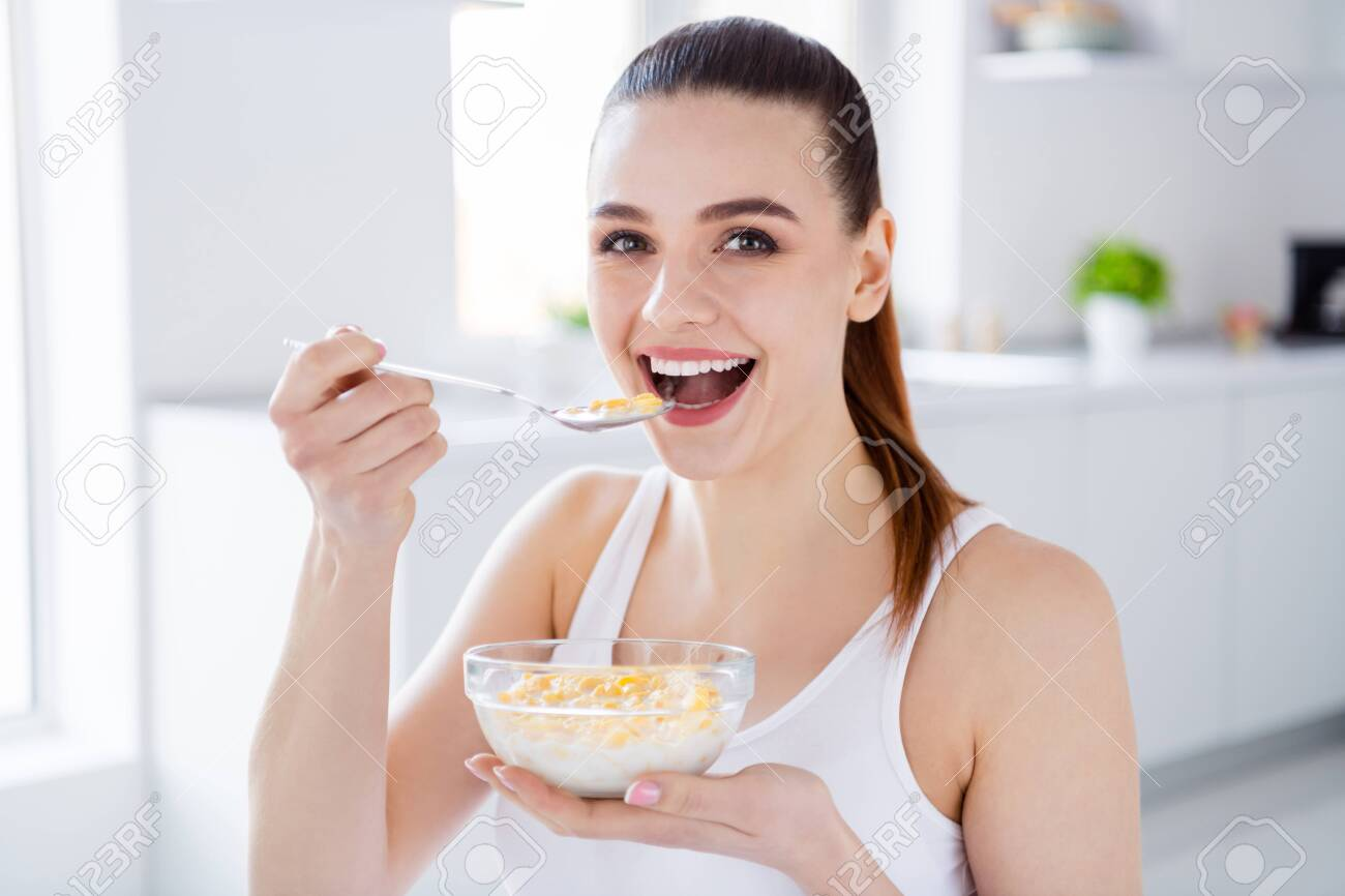 Closeup photo of pretty housewife lady sit morning kitchen have breakfast eat cereal corn flakes milk stay home distance remote work good mood quarantine time indoors - 148491072