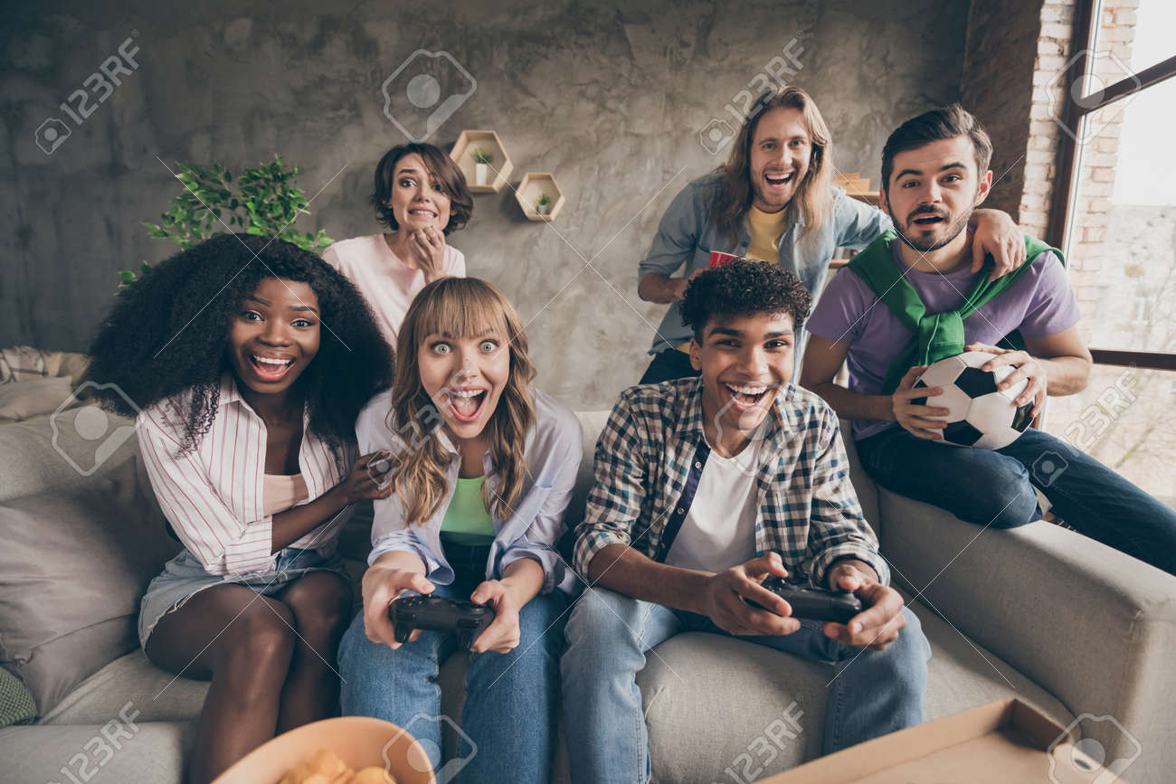 Portrait of attractive cheerful friends sitting on sofa having fun playing video game in house loft brick style interior indoors - 167176269